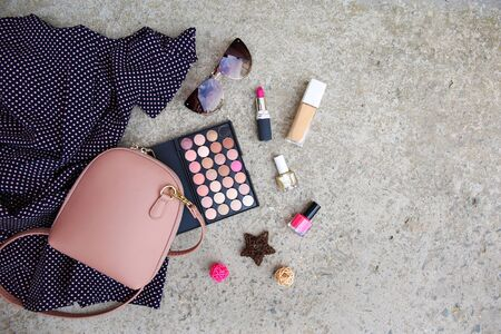 Summer women's clothing: dress, cosmetics, sunglasses, handbag on stone background. Top view. Flat lay.