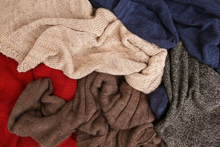 Pile of colorful warm clothes on wooden background. Top view. Flat lay. Banco de Imagens - 131145007