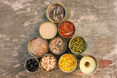 Different open canned food on old wooden background. Top view. Flat lay.