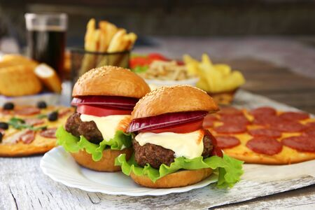 Fast food on old wooden background. Concept of junk eating. Banco de Imagens - 131145024