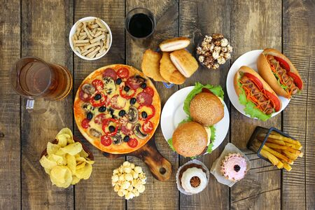 Fast food on old wooden background. Concept of junk eating. Top view. Flat lay.