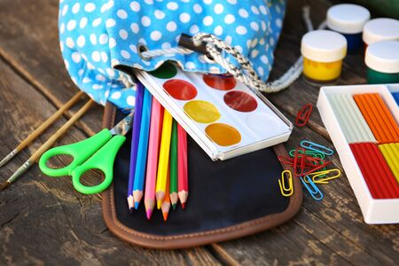 School supplies fall out of backpack on old wooden background. Banco de Imagens