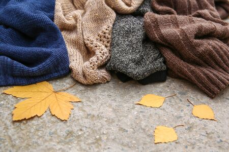 Pile of colorful warm clothes on stone background. Banco de Imagens