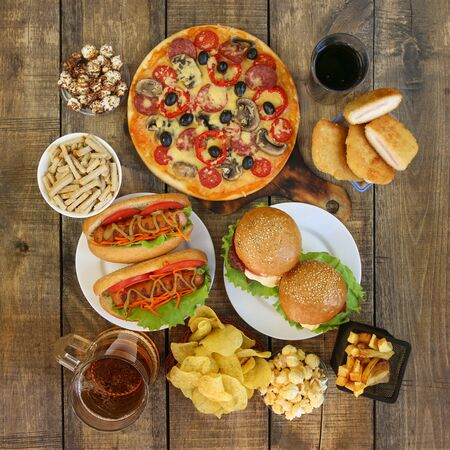 Fast food on old wooden background. Concept of junk eating. Top view. Flat lay. Banco de Imagens - 131145044