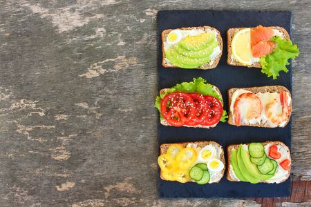 Different sandwiches on old wooden background. Top view. Flat lay.