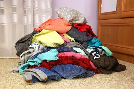 Pile of carelessly scattered clothes on floor. Banco de Imagens - 131145050