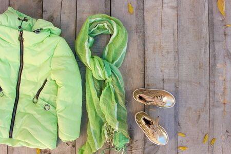Childrens autumn clothes and yellow leaves on old wooden background. Top view. Flat lay.