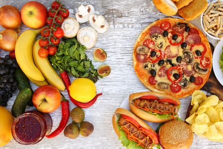 Fastfood and healthy food on old white wooden background. Concept choosing correct nutrition or of junk eating. Top view.