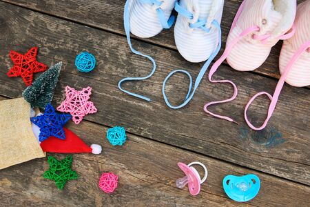 2020 new year written laces of children's shoes and pacifier on old wooden background. Top view. Flat lay. Banco de Imagens - 131145062