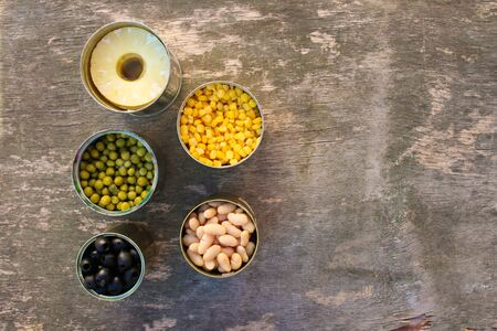 Different open canned food on old wooden background. Top view. Flat lay. Banco de Imagens - 131145063