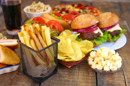 Fast food on old wooden background. Concept of junk eating.