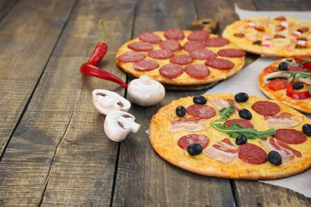Different pizzas on old wooden background. Banco de Imagens