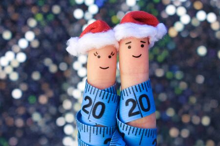 Fingers art of couple celebrates Christmas. Concept of man and woman laughing in New Year hats. Measuring tape is written 2020. Toned image. Banco de Imagens