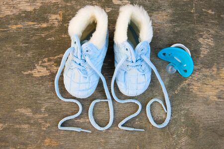 2020 new year written laces of children's shoes and pacifier on old wooden background. Top view. Flat lay. Banco de Imagens - 133020561