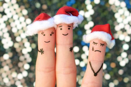 Fingers art of happy couple laughing in New Year hats. Woman is angry and jealous. Fingers art of couple celebrates Christmas.