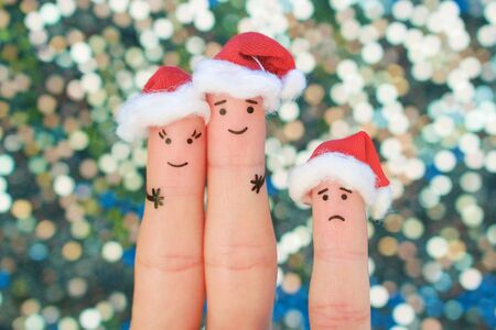 Fingers art of happy couple laughing in New Year hats. Man and woman hugs. Child is angry. Fingers art of couple celebrates Christmas. Zdjęcie Seryjne