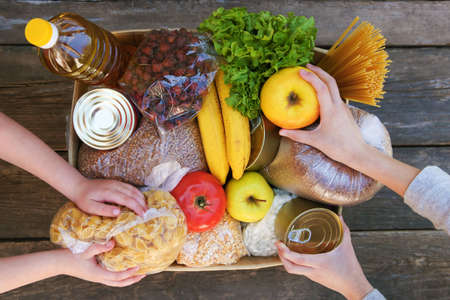 Donation box with food on old wooden background. Top view. Banco de Imagens