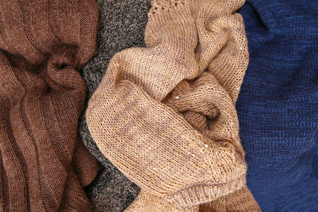 Pile of colorful warm clothes on wooden background. Top view. Flat lay.