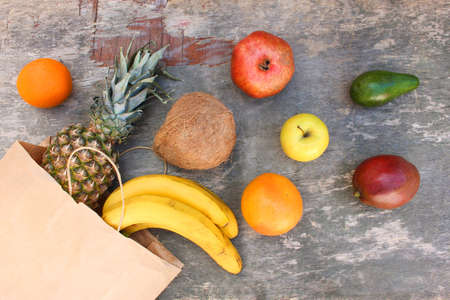 Paper bag with fruits and vegetables on old wooden background. Top view.