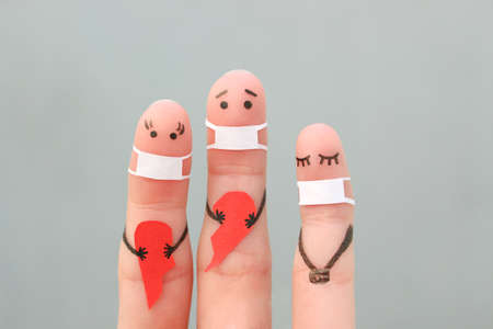 Fingers art of family in medical mask from COVID-2019. Concept of couple holding broken heart.