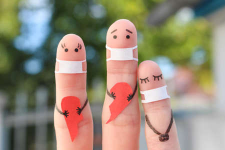 Fingers art of family in medical mask. Concept of couple holding broken heart.