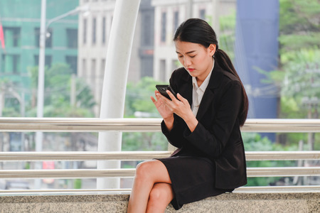 Businesswoman sitting and using  smartphone on city background