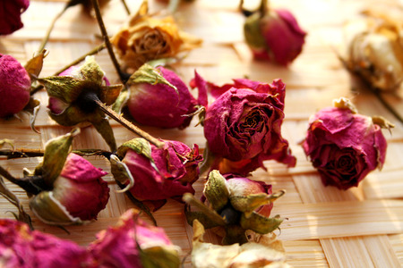 Small dried roses lie on a wicker basket Standard-Bild