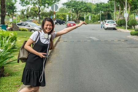 笑顔の女性を待って、タクシーを呼びかけ