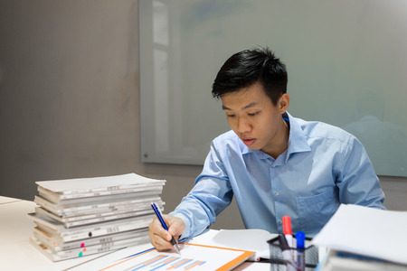Office employee reading sales report and writing notes Banco de Imagens - 88281666