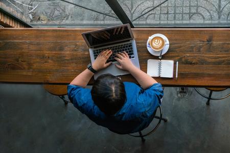 Freelancer joven asiático que trabaja en línea en su computadora portátil Foto de archivo