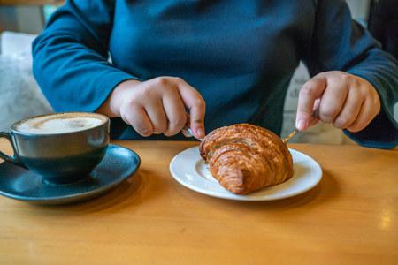 Junges Mädchen isst Croissant und trinkt Kaffee