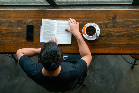 Top view of Asian man reading book and drinking coffee