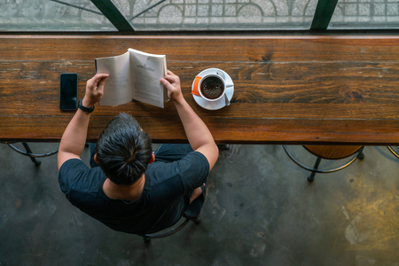Asian man read a book and drink coffee