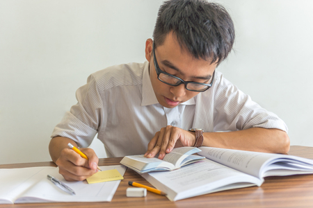 Young Asian man studying in the library