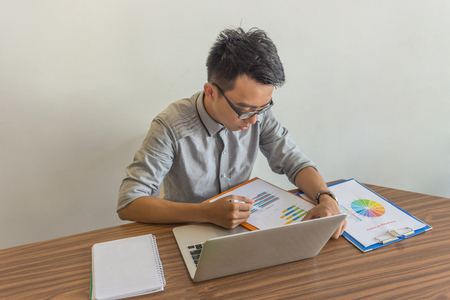 Young man working with financial document in office