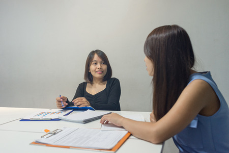 Asian employee discuss with teammate about work