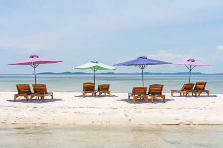 Four lounge chairs and umbrella at the white sand beach