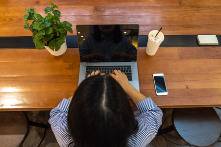 Freelancer using laptop while working on wooden table
