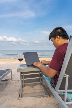 Rear view of young man using laptop on beautiful beach Imagens