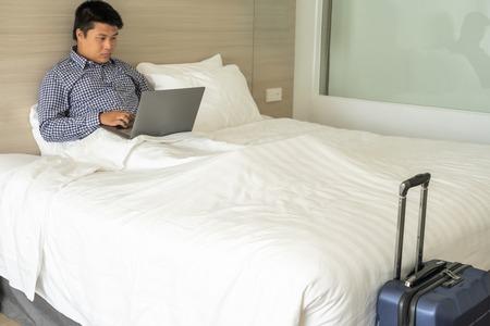 Giovane uomo d'affari che utilizza il computer portatile sul letto in viaggio d'affari Archivio Fotografico