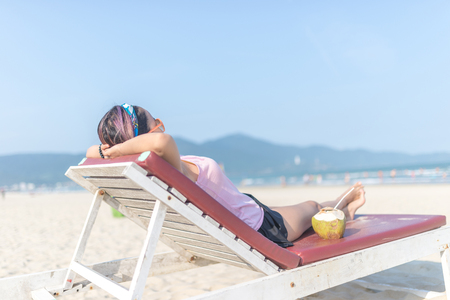 Asian woman enjoy summer vacation on beach with coconut juice