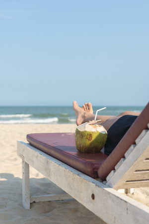 Close up of woman lying on beach chair with coconut Фото со стока