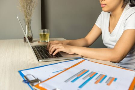 Freelancer woman typing on laptop keyboard next to graph business document
