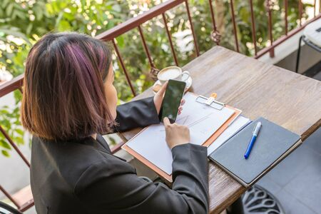 Woman using phone with document , notebook , coffee on table