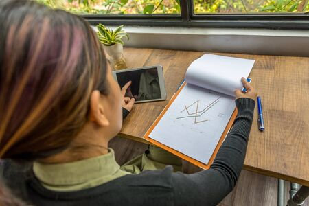 High angle view of freelancer working with tablet and document