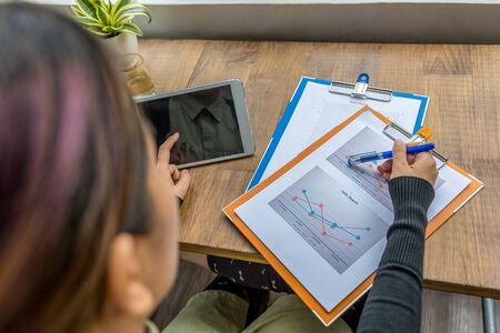 Top view of woman using tablet and pointing at diagram