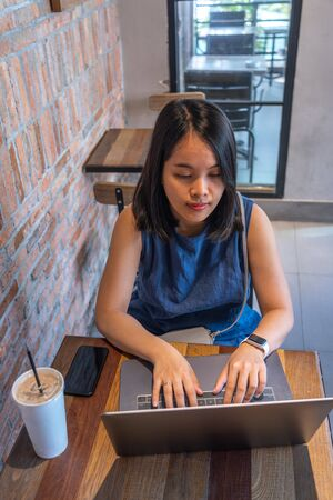 High angle view of woman using laptop at rustic cafe Imagens