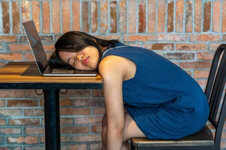 Tired Asian girl falling asleep on laptop keyboard at table Stok Fotoğraf