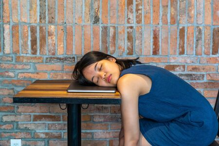 Restless woman falling asleep on laptop at rustic brick wall