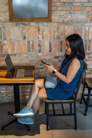 Young Asian woman sitting with laptop on wooden table